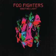 A collage of green blue and pink face pictures of the Foo Fighters members against a black background Above it is the title FOO FIGHTERS - WASTING LIGHT in red letters