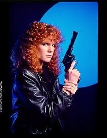 An image of a woman with bright red, curly hair. She is holding a gun and looking toward the camera.