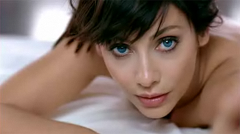 Imbruglia lying on a bed topless.