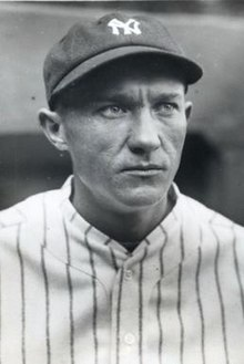"A close-up of a man wearing a baseball cap with an ""NY"" on the front and a pin-striped jersey looks to the right."