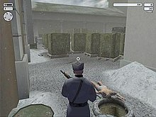 A man wielding gun looks across the unconscious, naked body of a guard in an outside storage facility.