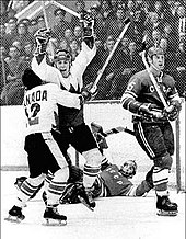 Henderson is embraced by teammate Cournoyer immediately following his winning goal. The Soviet goaltender lays prone in front of the net while another Soviet player skates away.