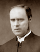 Bald white man in middle age, wearing clerical collar and black clothing