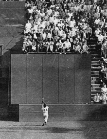Nearly at a wall, a baseball player reaches up underhanded to catch a ball falling towards him while over 30 feet above, several rows of fans stare down in amazement