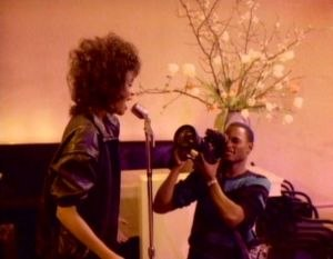 """You Give Good Love - Houston in the music video for """"You Give Good Love"""", tells the story of a romance with a cameraman."""