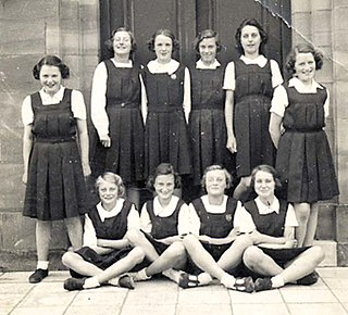 Gymslip sleeveless jumper or pinafore dress with a pleated skirt worn as school uniform for girls