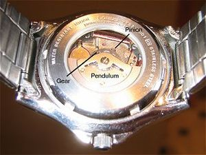 Automatic quartz - Lorus (a Seiko brand) watch with glass back, showing clearly the swinging pendulum and meshing gear and pinion of the Seiko Kinetic movement