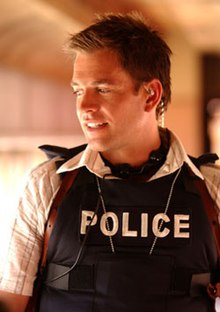 A man with short hair wearing a police bulletproof vest over a button-down shirt.