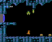A video game screenshot. A person in a powered exoskeleton travels through a cave, while winged monsters hang from the ceiling.