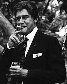 A middle-aged man of European descent smiles while holding a glass in his left hand and retrieving a cigarette from his mouth with his right. He is immaculately turned-out in a dark-coloured suit and looking to the viewer's left.