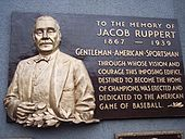 "A plaque commemorating Jacob Ruppert, which reads: ""Gentleman, American, Sportsman: Through whose vision and courage this imposing edifice, destined to become home of champions, was erected and dedicated to the American game of baseball"""