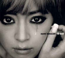 A dark, black-and-white up-close shot of Ayumi Hamasaki looking into the camera, with a teardrop trickling down one cheek.