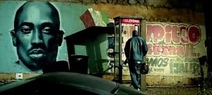 '03 Bonnie & Clyde - As Jay-Z and Beyoncé share an intimate moment in a phone-booth, a spray-painted mural is displayed, tributing Tupac Shakur.