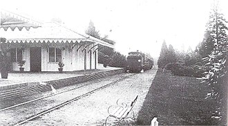 A train on a single rail track near a small white wooden station.