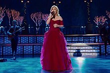 A blonde haired woman in a red dress performing in a Christmas decorated stage