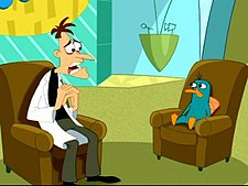 A cartoon Caucasian man wearing a white lab coat sits on a brown coach with a sad and sincere look on his face. Across from him is a green platypus bearing the same expression and on the same kind of couch. Behind them is a TV set with blue walls and a large yellow sign.