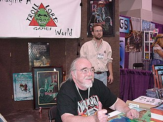 Gary Gygax - Gary Gygax at Gen Con in 2003. He is sitting in the Troll Lord Games booth with Stephen Chenault.