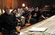 Four men sitting around a large mixing board.