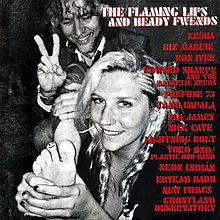 A black-and-white photo of Kesha holding her foot to the camera with a smiley face drawn on her toe, standing in front of Wayne Coyne who is giving a peace sign with his fingers and smiling. The title of the album and the collaborators are written in red to the right.