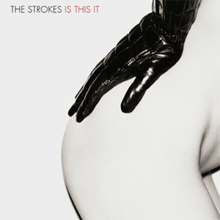 "Mostly white album cover containing, largely in the right-hand side, a woman's nude right bottom and hip, with a black leather-gloved hand resting on it. It is captioned ""THE STROKES IS THIS IT"" in the top left-hand corner."