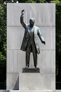 Statue of Roosevelt holding an arm up during an oration