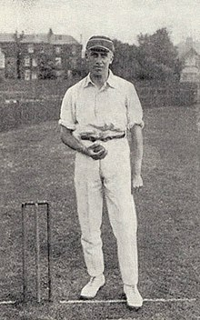 A man in a cricket cap holding a ball