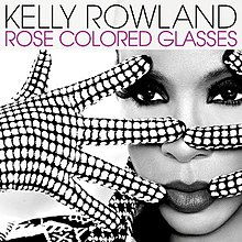 "A woman stands with only her face visible. She is wearing polka-dot gloves on her hands which she is holding in front of her face in a spread fashion. The image is black and white. In the foreground at the top, in black text, it reads the artist's name (Kelly Rowland). Directly beneath this it reads the name of the song, in pink text, ""Rose Colored Glasses""."