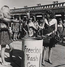 Women toss feminine items in a trash can as a form of protest about female sexualization and oppression