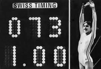 Perfect 10 (gymnastics) - Nadia Comăneci poses beside the scoreboard that recorded her perfect 10 as 1.00 (with no Olympic precedent, the hardware was not capable of displaying 10.00).