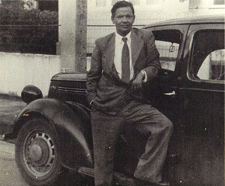 Seepersad Naipaul, father of V. S. Naipaul, and the inspiration for the protagonist of the novel, Mr Biswas, with his Ford Prefect. Seepersad Naipaul with Ford Prefect.jpg