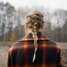 A picture of Swift's back. She is wearing braids and a plaid coat. The background is a blurred picture of a forest.