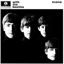 A black-and-white photograph of the Beatles' faces on a black background with the band members wearing black turtleneck sweaters