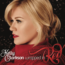 "A blonde haired woman whose neck is wrapped in a red scarf looking sideways against a dark background; below her, the word-marks ""Kelly Clarkson"" and ""Wrapped in"" are printed in stylized ""Feel Script"" and ""Bree"" typefaces aside a red ribbon-styled ""Red"" word-mark."