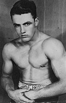Wrestler Stu Hart wearing an amateur wrestling championship belt, sometime between 1933 and 1936.jpg