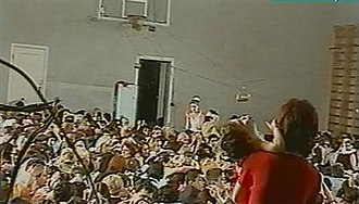 Beslan school siege - Hundreds of hostages packed into the school gym with wired explosives attached to the basketball hoop (a frame from the Aushev tape)