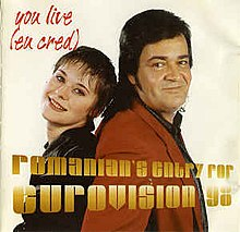 A shot of Olinescu and Adrian Romcescu standing side to side in front of a beige backdrop. Information on the song is superimposed on them in yellow and red letters.