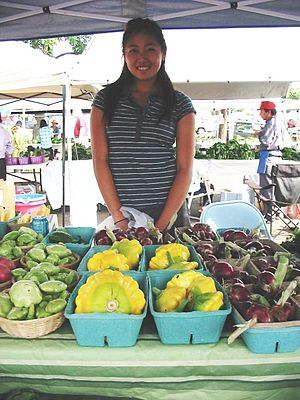 Frogtown, Saint Paul - A young Hmong-American woman selling produce at the Frogtown farmer's market