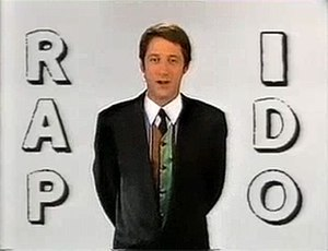 Rapido (TV series) - De Caunes presented and linked reports in front of the minimalist white lettered background seen here