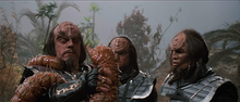 Two aliens watch their leader fight a slimy worm that has wrapped itself around his arm and neck. The aliens are wearing metallic armor with decorative script on their gauntlets; their hair is long and black, and their foreheads are bumpy and ridged.