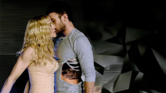 4 Minutes - A still from the music video showing Madonna and Timberlake. The black background is seen behind Timberlake, devouring his sides.