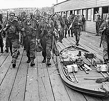 Armed soldiers march past a collapsed boat containing equipment