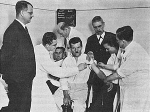 Julius Wagner-Jauregg - Wagner-Jauregg (center right in black jacket) watching a transfusion from a malaria patient (rear of the group) to a neurosyphilis victim (center) in 1934