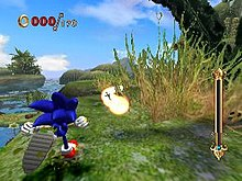 The hedgehog runs up a grassy hill which veers off to the right, partially obscured by a bush. He prepares to run into a trail of bright spheres resembling pearls. The area overlooks a swamp and the deep daytime sky.