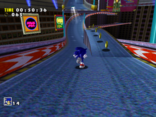 Gameplay screenshot of Speed Highway, one of the levels in Sonic Adventure. In this image, Sonic runs on a road, to a line of rings. The HUD shows a timer, the amount of rings, and the player's lives.