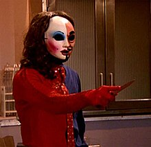 A figure wearing an outfit that is half red and half blue. The figure is wearing a mask that is split between a more masculine half and a more feminine half. The figure is pointing a knife towards an unknown target.