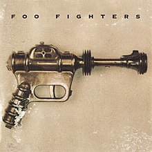 A toy of a futuristic pistol in front of a beige background The title Foo Fighters is seen atop the toy