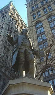 Bronze statue of Benjamin Franklin holding a copy of the Pennsylvania Gazette by Ernst Plassman, commissioned as a gift to the City of New York from Albert De Groot in 1872 when the area was known as Printing House Square, corner of Pace Plaza, (Park Row and Spruce Street), New York City campus.
