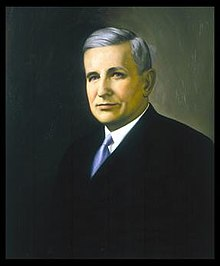 A color portrait of a gray-haired man in his early sixties wearing a suit