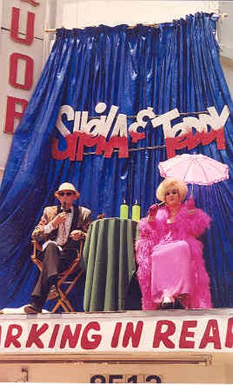 "April Winchell - Ted Hardwick and April Winchell (as ""Teddy Towne"" and ""Sheila Sands"") provide color commentary for the 1998 Christopher Street West Gay Pride Parade, in West Hollywood, California, from atop the Monaco Liquor Store sign on Santa Monica Boulevard."
