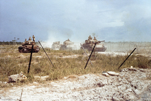 Four main battle tanks on a road kick up dust as they move towards a defensive position.